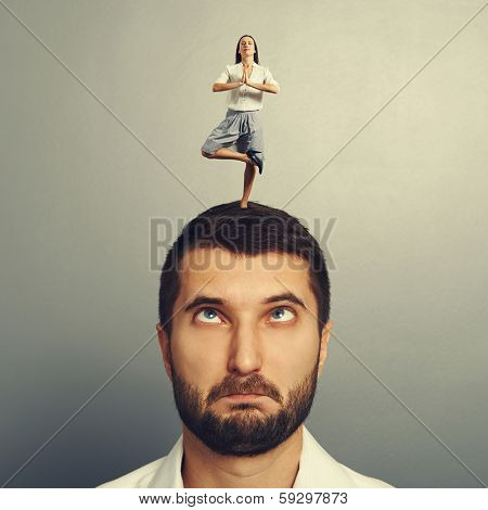 small meditation woman standing on the head of foolish man