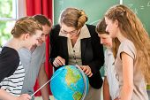 Students or pupils having group work while geography lesson and the teacher test or educate them in school or class poster