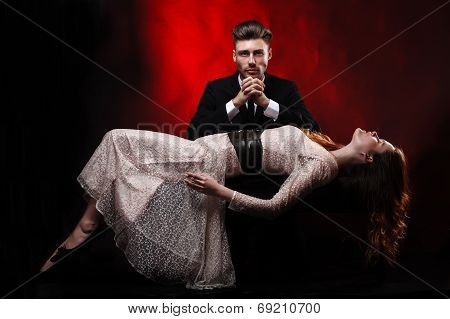 Portrait of professional hypnotist on black background working with young woman