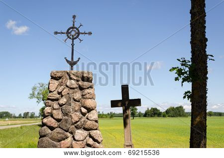Stone Monument With Metal Squirm Cross In Nature
