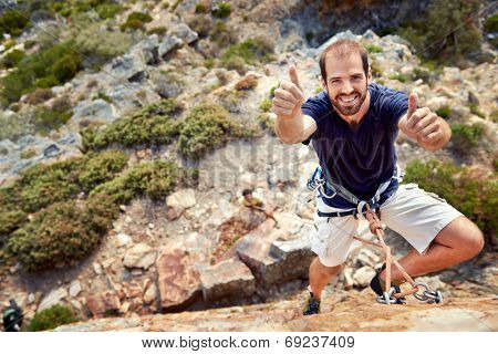 A rock climber with rock climbing equipment on holding a thumbs up and smiling at  the camera