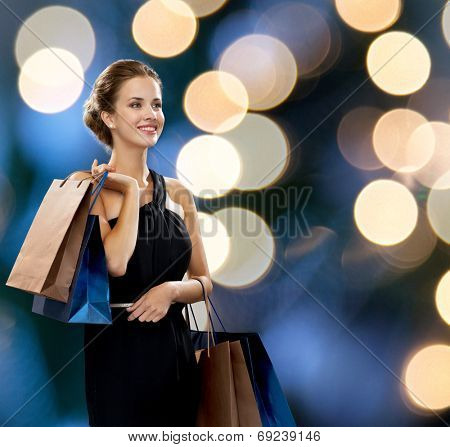 shopping, sale, gifts and holidays concept - smiling woman in dress with shopping bags over black background