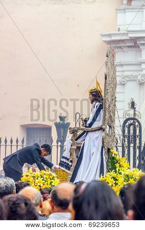 LIMA, PERU, MAY 25, 2014 - Man decorates Statue of Christ with flowers during religious procession