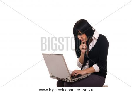 Beautiful young girl sitting on the floor with her laptop