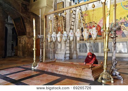 JERUSALEM,ISRAEL - SEPTEMBER 3, 2012: The pilgrim in red clothes passionately prays under icon lamps in the church of the Holy Sepulcher . The oldest Christian sanctuary - Stone of Unction