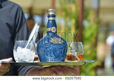 TSELEEVO, MOSCOW REGION, RUSSIA - JULY 26, 2014: Waiter offers the whiskey Royal Salute to the guests of the British Polo Day. This brand of Scotch whisky produced by Chivas Brothers