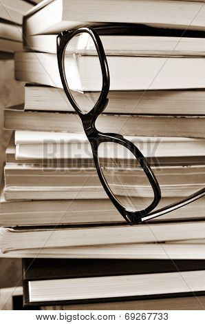 a pair of eyeglasses on a pile of books, in black and white