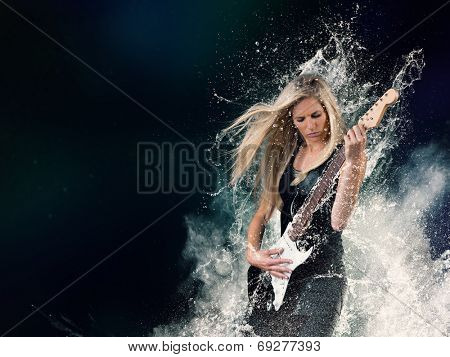 Beautiful young woman playing on electric guitar in water splashes, isolated on black background