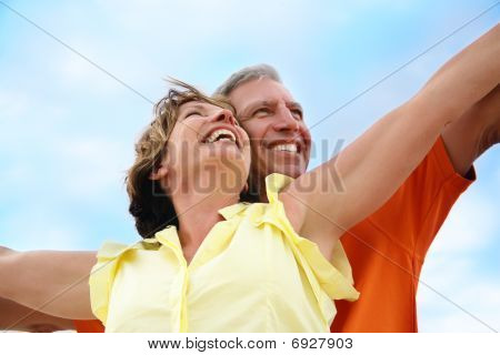 Mature couple standing with arms outstretched.