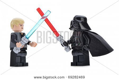 Ankara, Turkey - April 06, 2013: Lego Star Wars minifigure Darth Vader and Luke Skywalker are fighting with sword in front of other Star Wars characters isolated on white background.