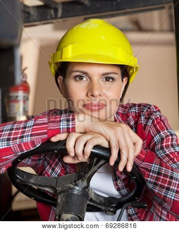 Portrait of confident female engineer wearing hardhat while leaning on steering wheel of forklift in workshop