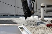 """Unidentifiable workers use """"Hot Tar"""" aka """"Hot Mop"""" to lay down Molten Tar, Asphalt Sheets and Pea Gravel on a Flat roof on a Hot Summer day in Southern California. Roofs are important on houses poster"""