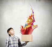 Cute boy splashing colorful paint from carton box poster