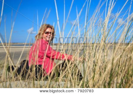 Woman Sitting In The Sand Dunes On The Beach