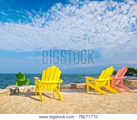 Yellow and pink colorful lounge chairs on a beach in Florida