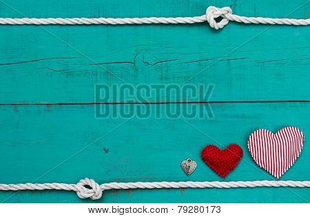 Blank blue wood sign with red hearts and lock by white rope border with knots