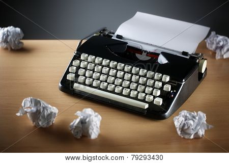 Frustration stress and writers block with old typewriter on desk and crumpled paper ball