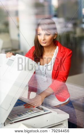 Pretty young female college student/secretary using a copy machine (shallow DOF; color toned image)