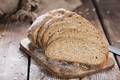 Bread on dark rustic wooden background as detailed close-up shot poster