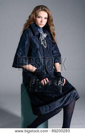 Full body fashion model in fashion dress holding purse sitting cube