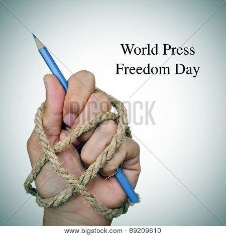the text world press freedom day and the hand of a man, completely tied with rope, holding a pencil, depicting the idea of oppression or repression