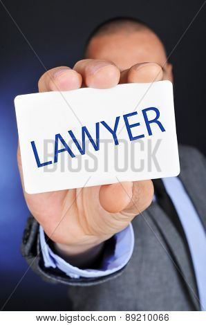a young caucasian man wearing a gray suit shows a signboard with the word lawyer written in it