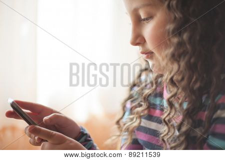 Little girl looking at smart phone