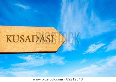 Wooden arrow sign pointing destination KUSADASI TURKEY against clear blue sky with copy space available. Travel destination conceptual image poster