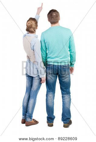 young couple pointing at wal Back view . Rear view people collection.  backside view of person.  Isolated over white background. Man and woman standing side by side and looking curiously at the top.