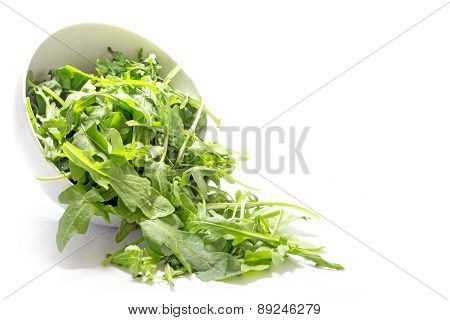 Rocket Salad Leaves, Rucola Or Arugula, Falling From A Ceramic Bowl, Isolated On  White