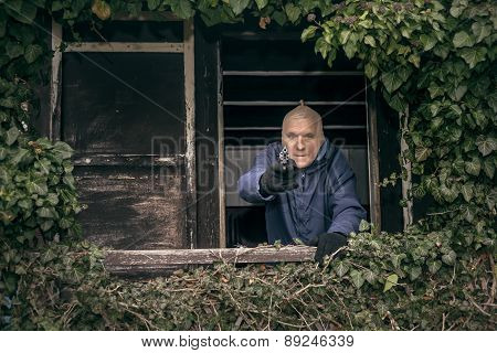 Masked senior escapee man aiming a gun hiding on overgrown porch of old cabin. poster