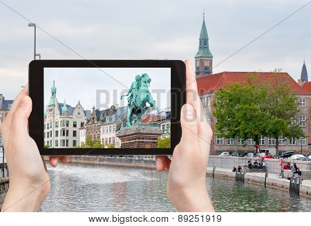 travel concept - tourist takes picture of Statue of Absalon on Hojbro square and Frederiksholms Kanal in Copenhagen Denmark on tablet pc poster