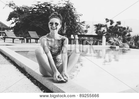 Young pretty woman with perfect tanned body lying on yellow air mattress in the pool in summer and having fun. Outdoor fashion black white portrait of happy girl poster