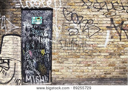 Vandalised brick wall and door