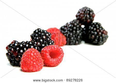Blackberries and raspberries on white background