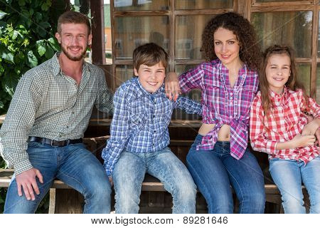 family of four sitting on a bench on background of wooden window