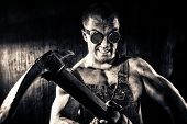 Muscular dirty coal miner with a pickaxe over dark grunge background. Mining industry. Art concept. Toned photo, old style. poster