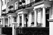 Black and white monochrome photograph picture of  expensive old fashioned typical Regency Georgian terraced town houses building architecture in fashionable Notting Hill, Kensington, London, England, UK. These residential homes are often turned into apart poster
