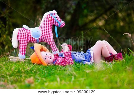 Little Girl Playing With Toy Horse In Cowboy Costume