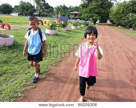 Schoolkids Walking To School On Country Road Under The Sunlight
