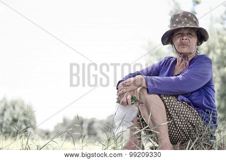 Old Woman Sat Smiling In The Field.
