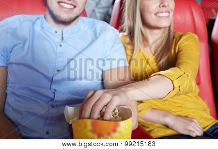 entertainment, leisure and people concept - close up of happy couple watching movie and eating popcorn in theater or cinema