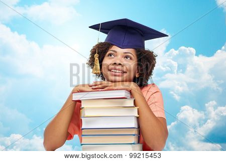 education, school, knowledge and people concept - happy smiling african american student girl in bachelor cap with books sitting at table and dreaming over blue sky and clouds background poster