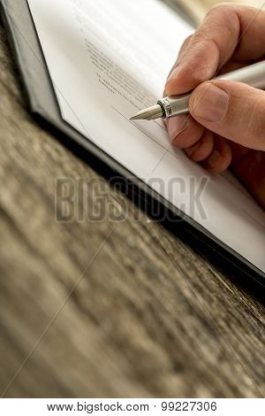 Closeup of male hand signing business contract application subscription form or insurance papers with fountain pen on textured old rustic wooden desk. poster
