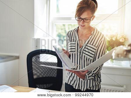 Young Woman Reading Notes In An Office Binder