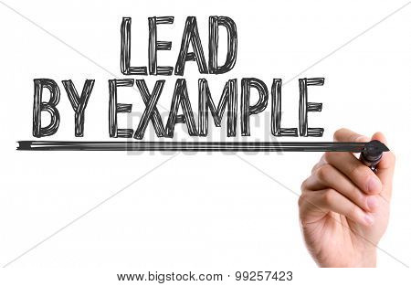 Hand with marker writing the word Lead By Example