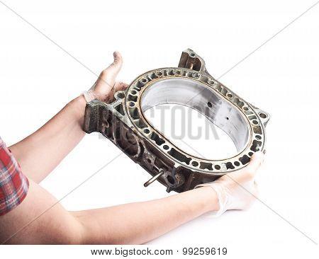 Worker's male hands holding a carburetor's detail