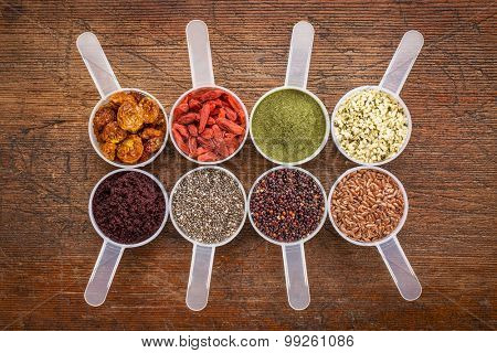 superfood abstract (wheatgrass, acai berry, goji berry, flax seed,chia seed, goldenberry, hemp seed, quinoa grain) - top view of measuring scoop against rustic wood
