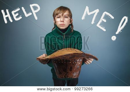Teen boy homeless asking for help holding a hat inscription hel