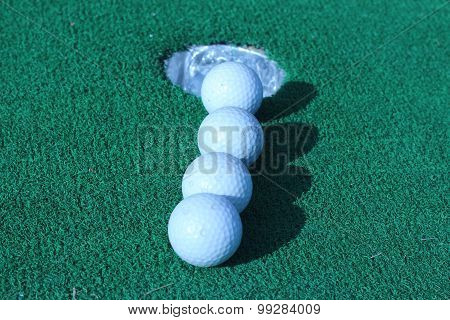 Wood And Golf Balls On The Green Grass